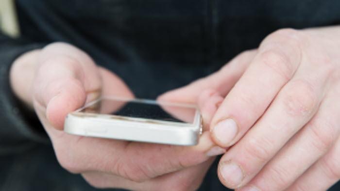 Händer håller i en telefon