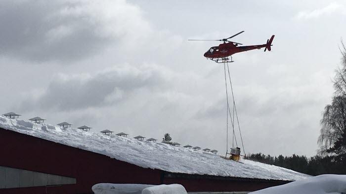 Helikopter skottar snö från ladugårdstak