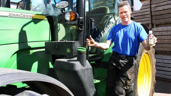 Mikael Säfström håller i en flaska HVO vid sin traktor