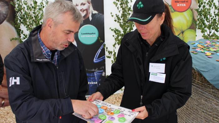 Maria Jonsson delar ut knappar på Mittia: Gård & Skog