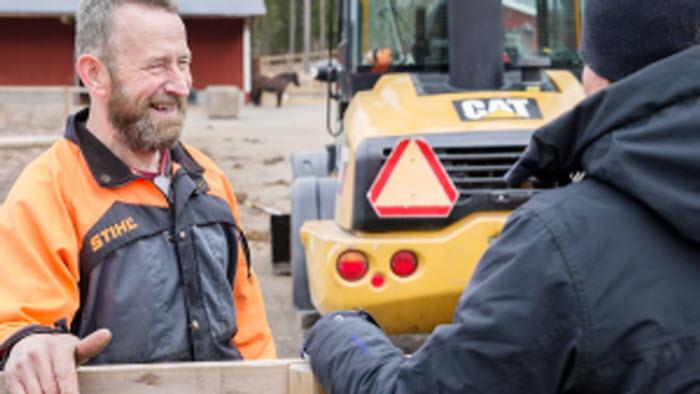 Två företagare samtalar på hästgård med traktor i bakgrunden