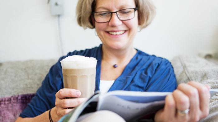 Kvinna läser tidning och dricker latte