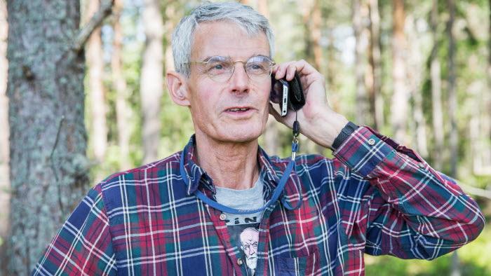 Skogsägare pratar i telefonen i skogen
