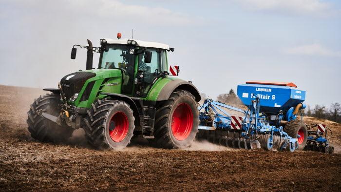 Traktor harvar på fält.